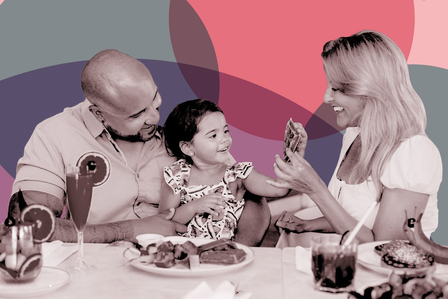two adults sit at a table full of food with a small child as they smile