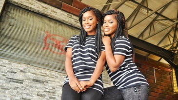 Two identical twin women of color stand in front of a gray brick wall, wearing striped shirts and braided hair.