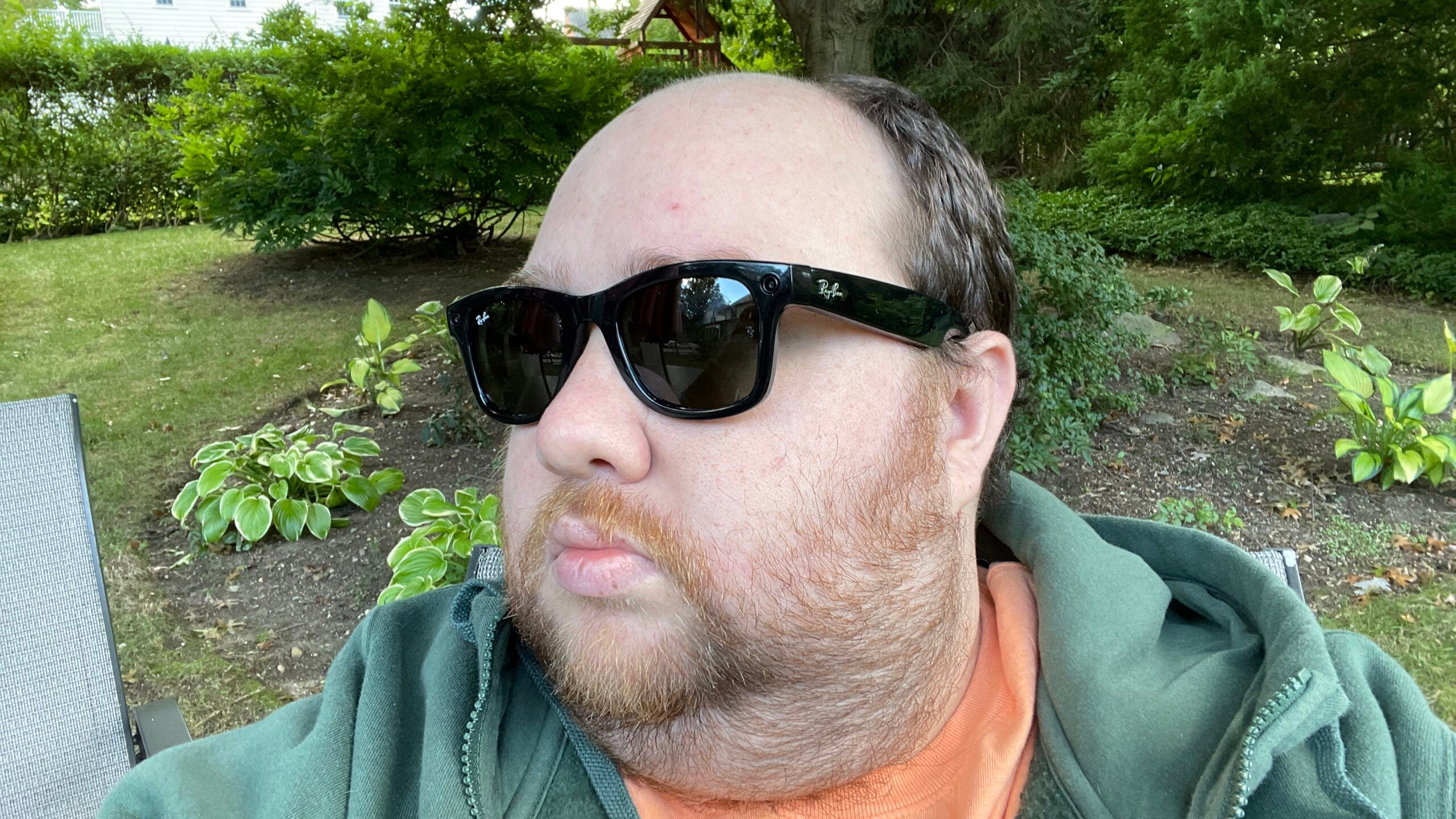 A man wearing Ray-Ban stories sunglasses in a garden