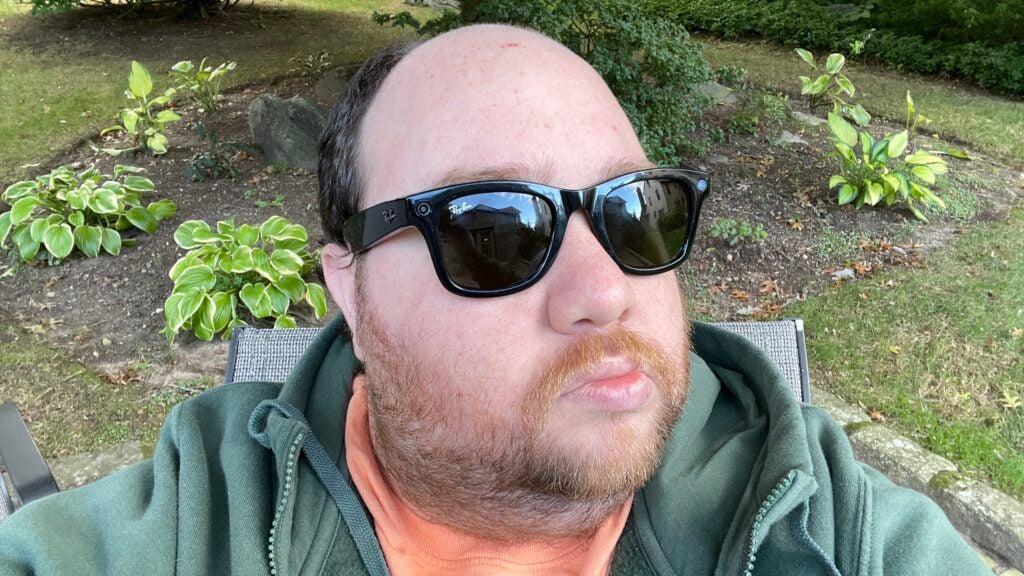 Man in green hoodie wearing Ray-Ban  Stories sunglasses.