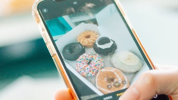 A person holding an iPhone and taking a picture of some doughnuts.
