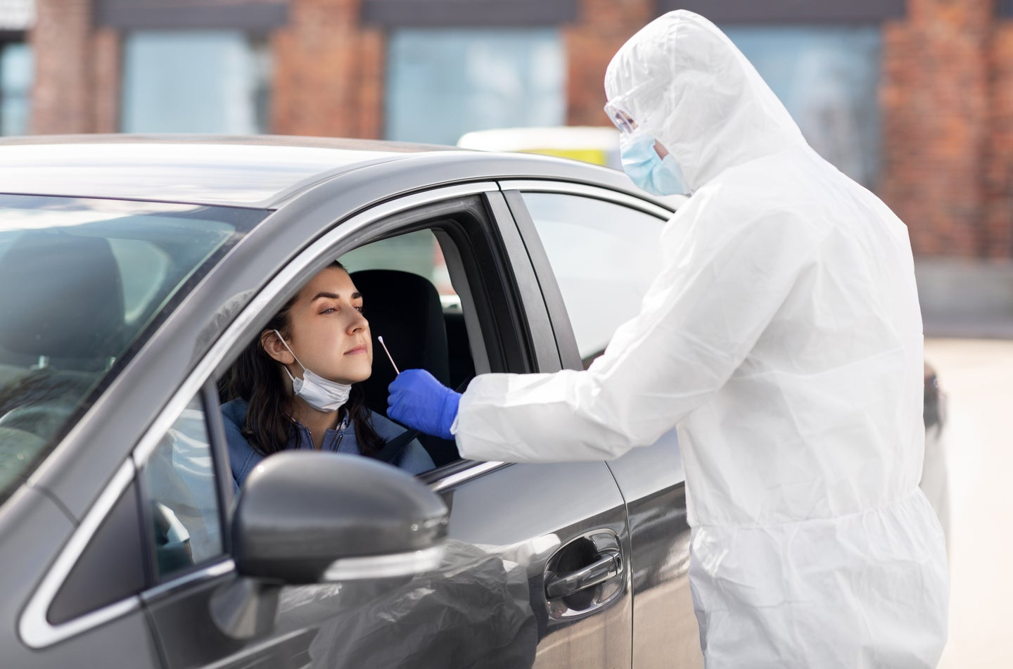 person in car gets covid nose swab test
