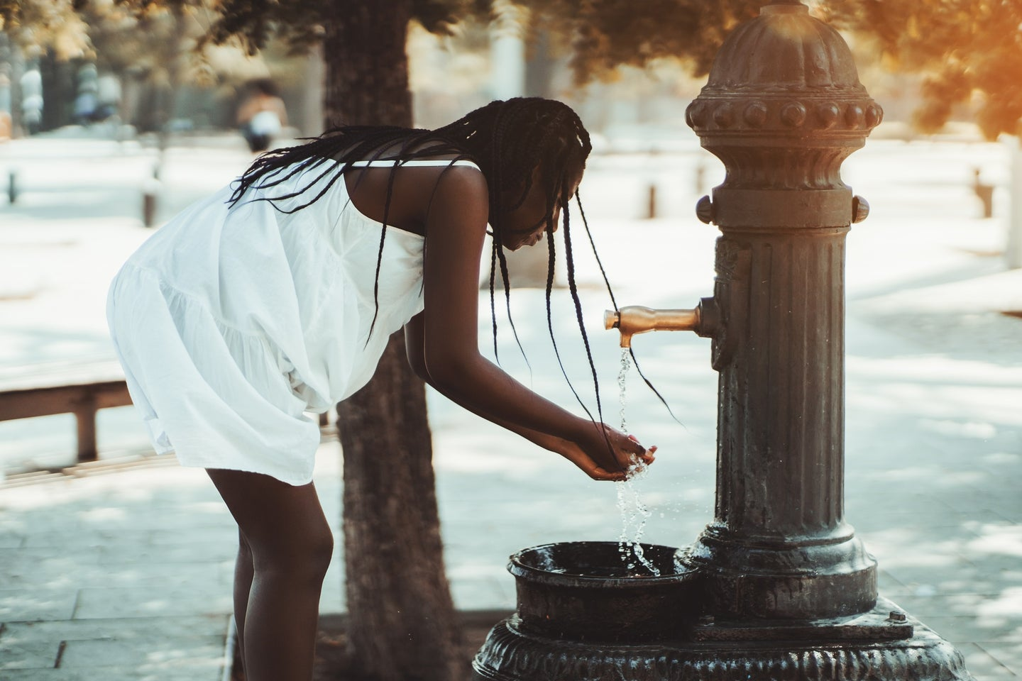 Black person in white dress and with long hair stooping over a city water fountain in the summer heat