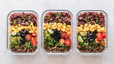 Row of neatly arranged food containers with salad.