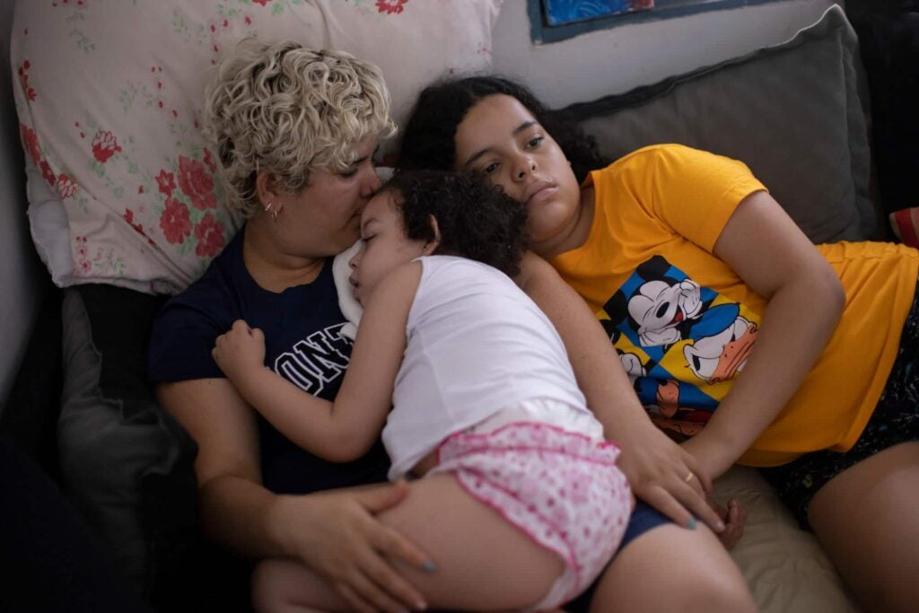 Brazilian mother sitting on couch with two daughters