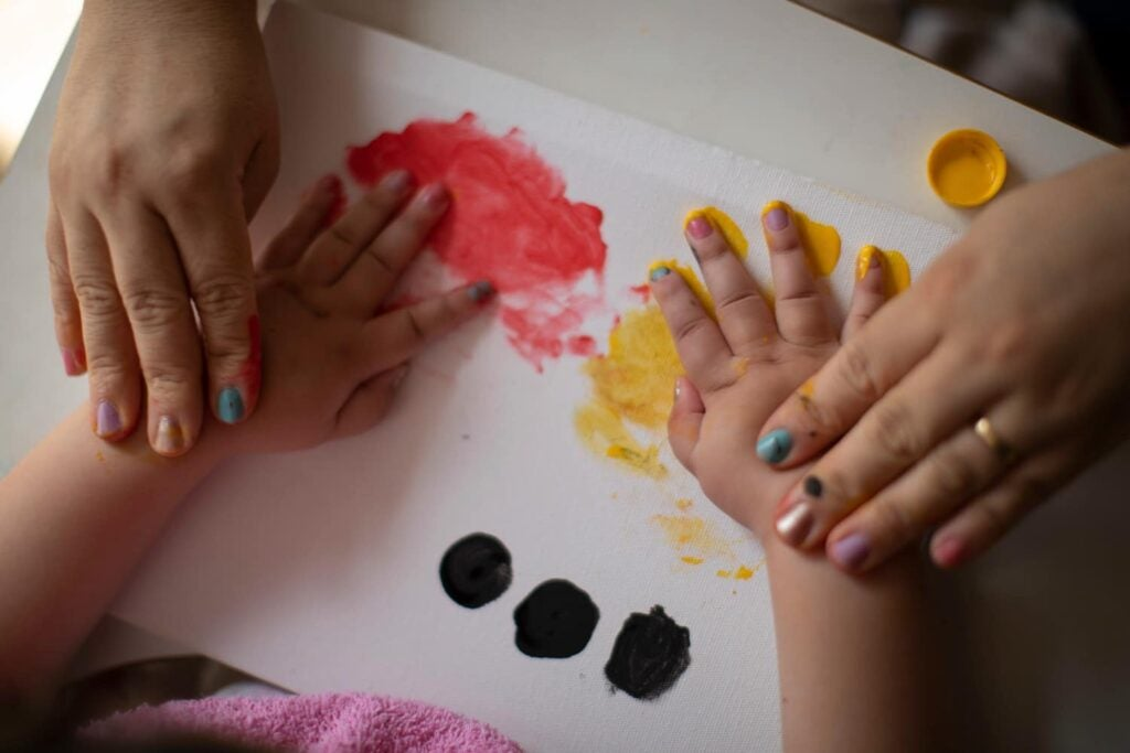 Baby with Zika congenital disease finger painting with mother