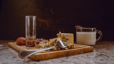Blue cheese on a charcuterie board with an empty glass.