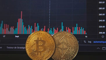 Bitcoins in front of a Bloomberg terminal