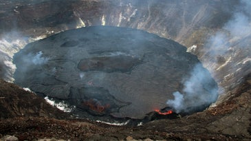 A large black crater in a volcano with smog and lava