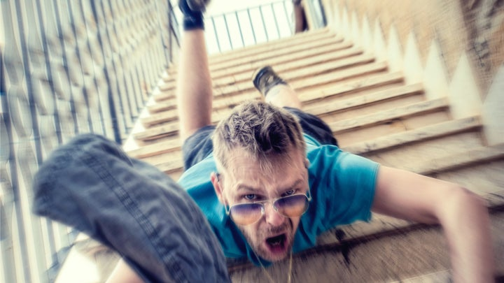 A man wearing sunglasses, a blue t-shirt, and shorts falling face-first down some concrete exterior stairs, while dropping a pair of jeans.