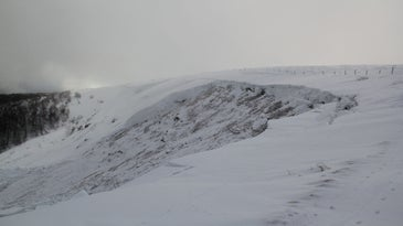 the aftermath of an avalanche on a snowy mountain, with rocks and grass exposed where a ledge of snow is missing