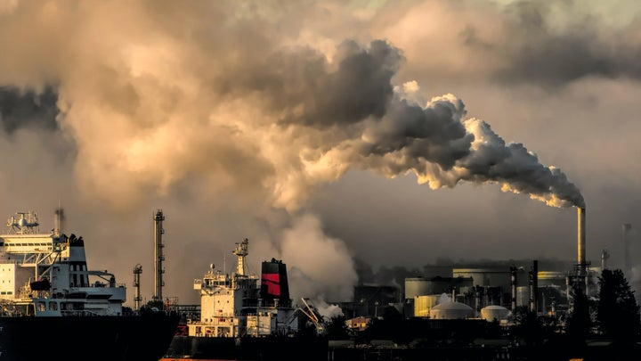 Smoke stacks emit greenhouse gas emissions that fuel climate change over a city waterfront